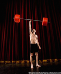 Funny picture of a skinny little guy lifting a huge set of barbells up over his head with only one arm. The wimpy guy is wearing a pair of black shorts and is bare chested. Funny body builder photo.
